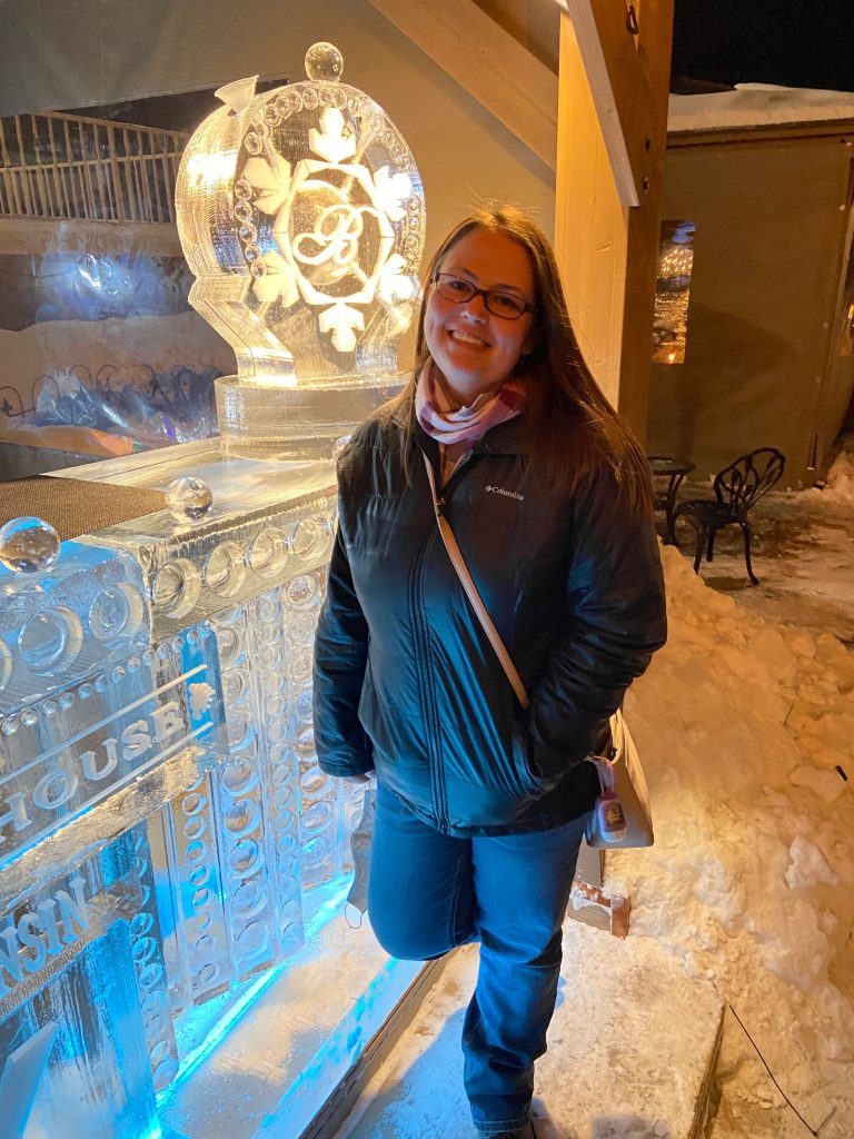 Woman at Baker House Ice Bar in winter jacket during Lake Geneva Winterfest. Standing next to ice bar with a block of ice that has a luge in it for drinks.