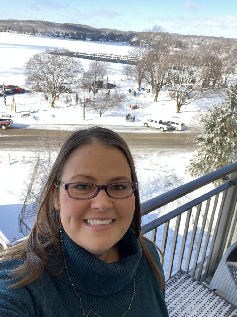Woman on balcony overlooking the Flat Iron Park during the Lake Geneva Winterfest. Teams can be seen on the ground working on their snow sculptures.