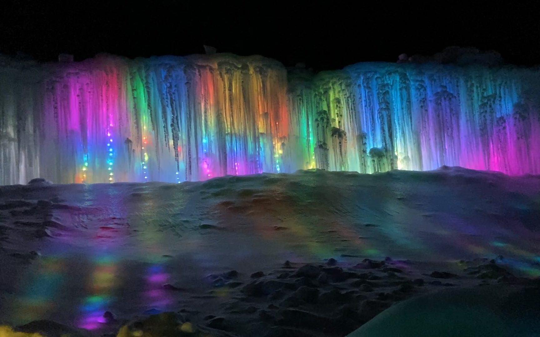 Long wall of large icicles with various LED light colors shining through them on a dark night at the Ice Castles in Lake Geneva.