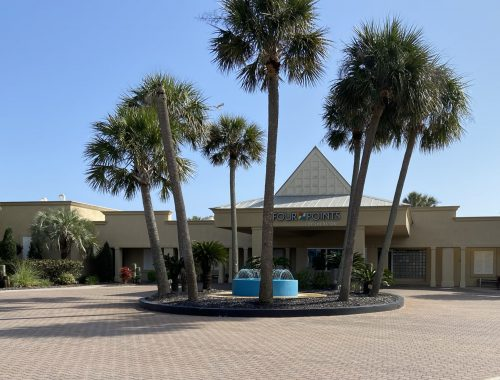 Entrance to the Four Points in Fort Walton Beach. Palm trees and a water fountain.